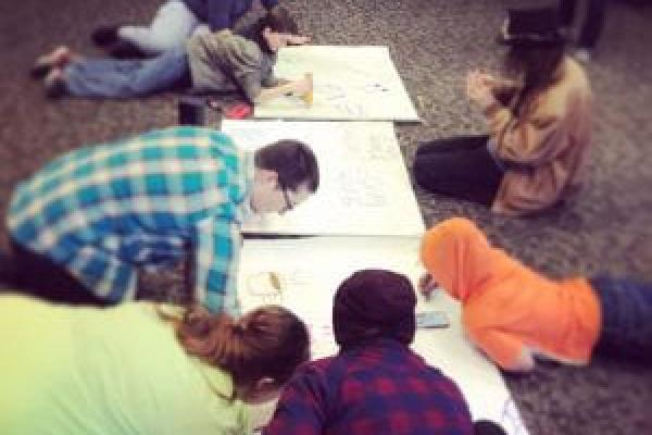 Several students drawing on shared paper