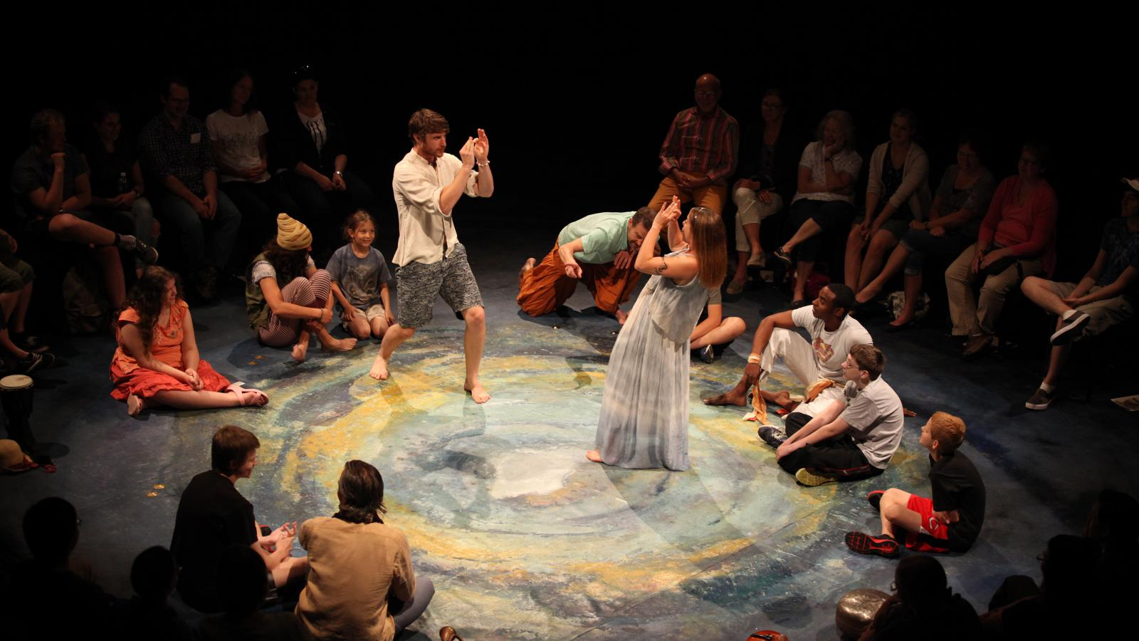 Two actors perform in The Tempest for an audience of young people on the autism spectrum who are seated on the stage in a circle.