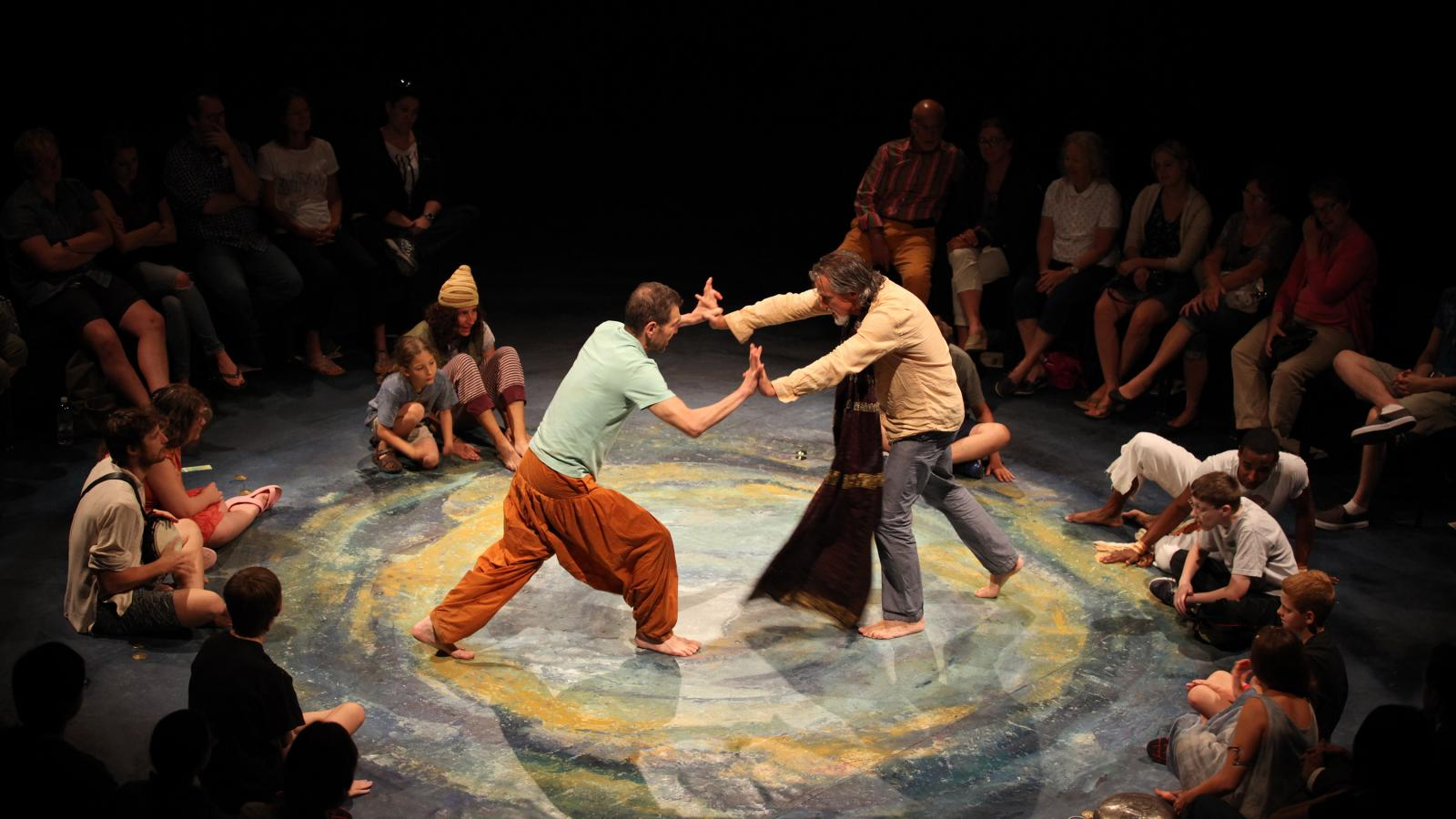 Two performers press into each other in The Tempest as an audience encircles the performing space.