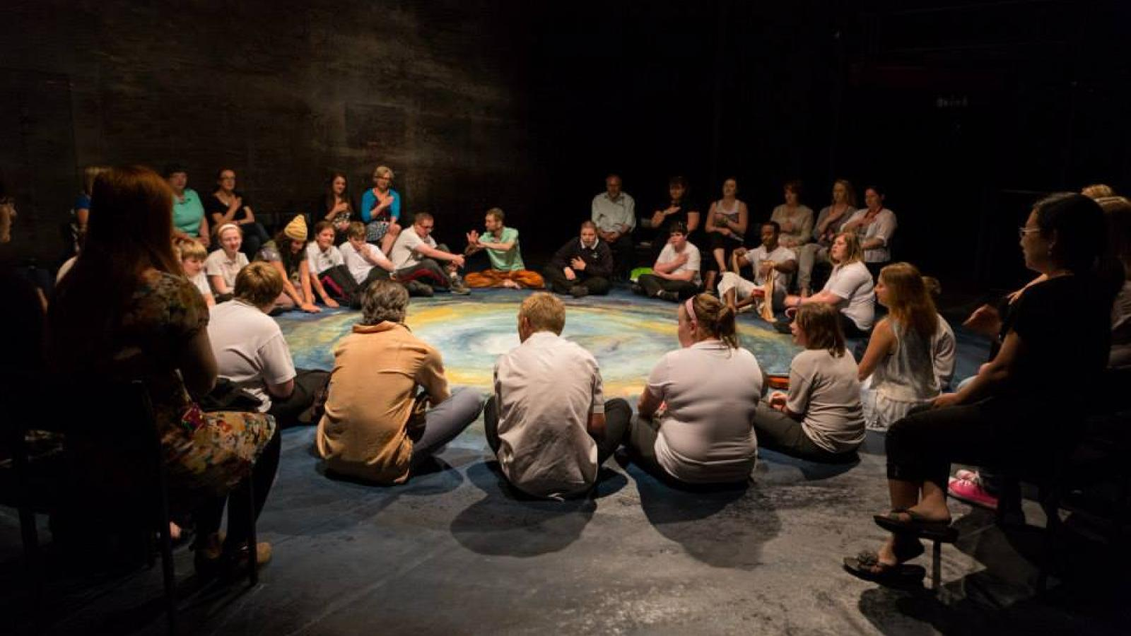 Young people on the autism spectrum sit in a circle onstage about to watch The Tempest.